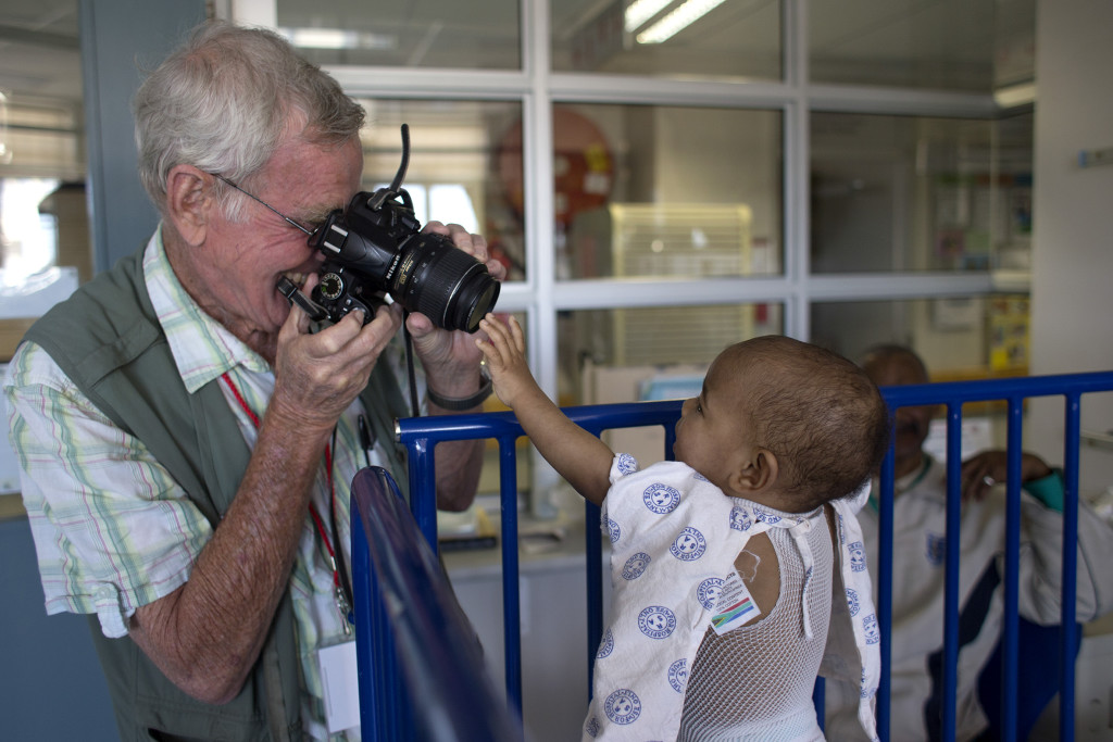 SOUTH AFRICA, Cape Town: A child reaches out to touch Retired Royal Air Force pilot Wouter van Warmelo's camera as he takes a photograph at the Red Cross War Memorial Children's Hospital on 30 November 2015. Wouter van Warmelo has been photographing patients at the hospital since September 2009 and has taken more than 10 400 photographs of children as part of the hospitalÕs family support programme run by Non Profit Organisation: Friends of the Children's Hospital. Orms Pro Photo Warehouse sponsors the photography project and has printed more than 22 000 prints which are given to the children and their families for free. PHOTO: JENNIFER BRUCE/CSR Newsroom