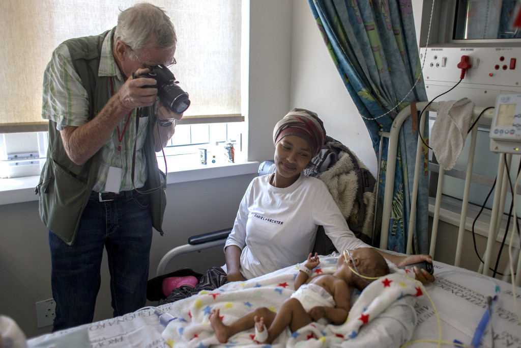 SOUTH AFRICA, Cape Town: Retired Royal Air Force pilot Wouter van Warmelo takes a photograph of a mother and her child at the Red Cross War Memorial Children's Hospital on 30 November 2015. Wouter van Warmelo has been photographing patients at the hospital since September 2009 and has taken more than 10 400 photographs of children as part of the hospital's family support programme run by Non Profit Organisation: Friends of the Children's Hospital. Orms Pro Photo Warehouse sponsors the photography project and has printed more than 22 000 prints which are given to the children and their families for free. PHOTO: JENNIFER BRUCE/CSR Newsroom