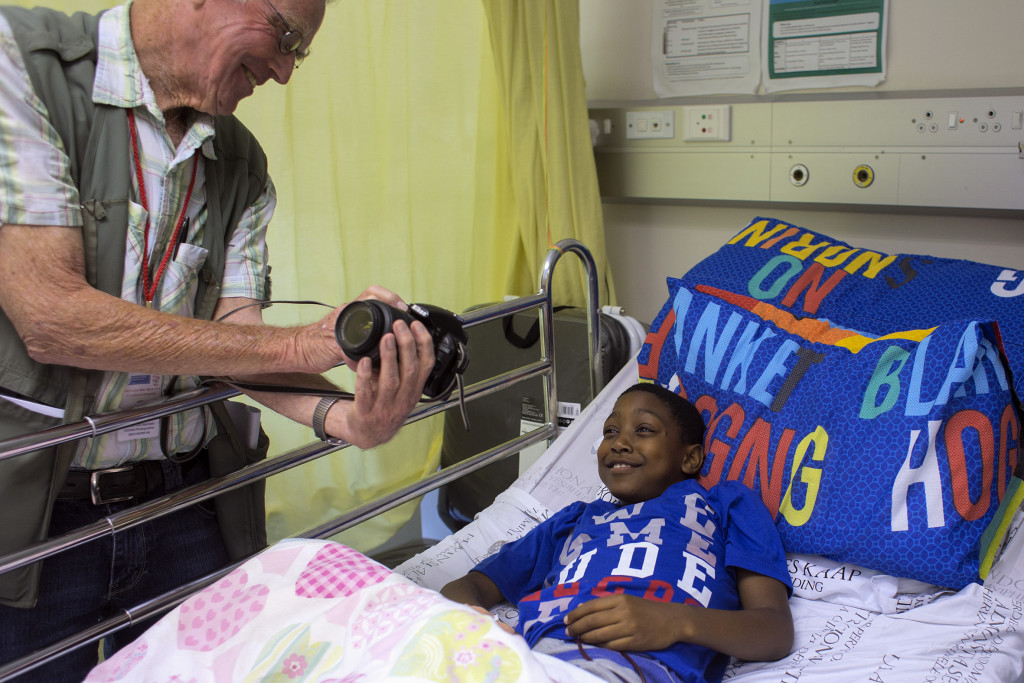 SOUTH AFRICA, Cape Town: Retired Royal Air Force pilot Wouter van Warmelo shows a patient at the Red Cross War Memorial Children's Hospital a portrait he's just taken of the child on 30 November 2015. Wouter van Warmelo has been photographing patients at the hospital since September 2009 and has taken more than 10 400 photographs of children as part of the hospitalÕs family support programme run by Non Profit Organisation: Friends of the Children's Hospital. Orms Pro Photo Warehouse sponsors the photography project and has printed more than 22 000 prints which are given to the children and their families for free. PHOTO: JENNIFER BRUCE/CSR Newsroom